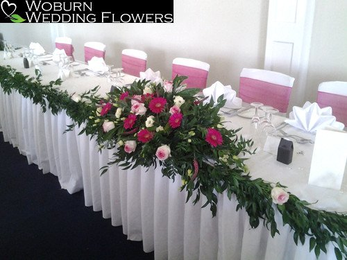 Top table arrangement with Gerbera, Rose and Freesia with a Rose decorated garland.