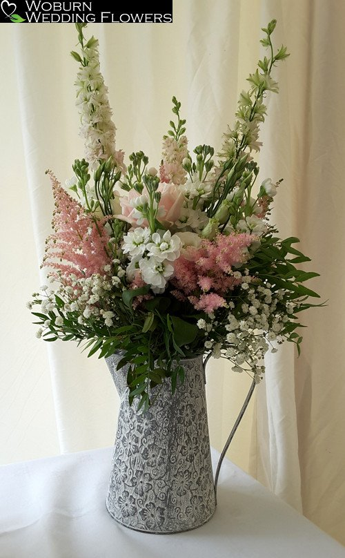 Stocks, Astilbe, Lizzianthus, Larkspur and Rose arrangement in jug.